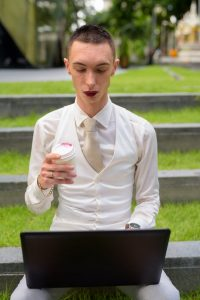 man in white suit sitting on a park bench with his coffee cup looking at his computer